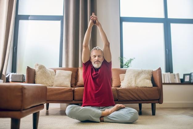 Joga. siwy mężczyzna siedzi na podłodze i robi jogę