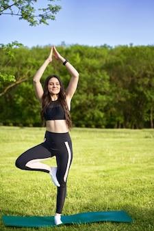 Joga. sportowa dziewczyna robi rozciągać outdoors, zanim ćwiczy joga na naturze