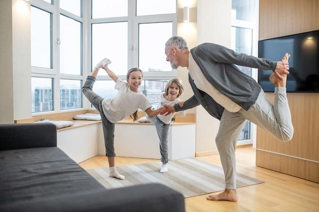 Joga w domu. tata i jego dzieci uprawiają razem jogę w domu i wyglądają na zaangażowanych