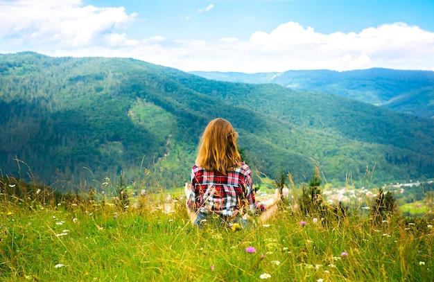 Joga w górach. piękna dziewczyna medytuje w asanie. niesamowita letnia przyroda wokół. koncepcja harmonii i wanderlust. hipsterskie podróże. stylowa kobieta, ciesząc się życiem.
