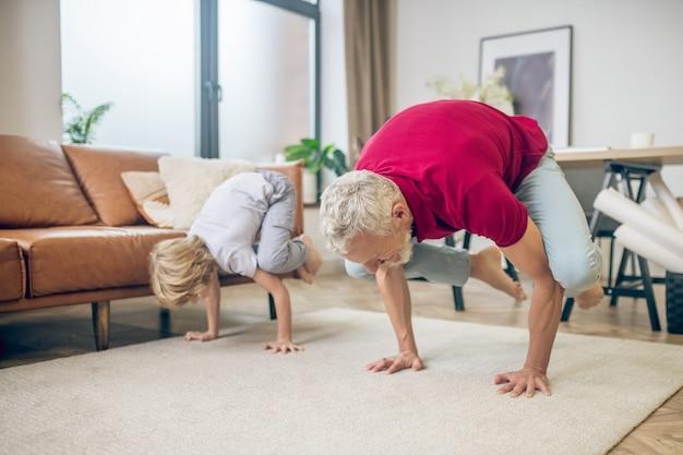 Joga z synem. siwowłosy sprawny mężczyzna robi jogę razem z synem