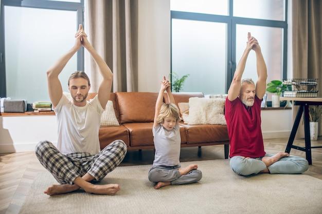 Joga. zróżnicowana rodzina uprawia jogę z dzieckiem i wygląda spokojnie