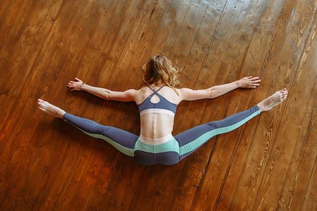 Jogin leży na brzuchu w pozycji do rozciągania kończyn