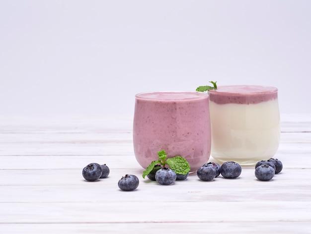 Jogurt biały i jagodowy jogurt na drewnianym stole
