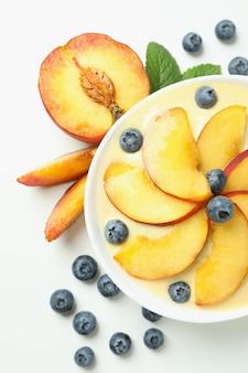 Jogurt brzoskwiniowy i składniki na białym tle
