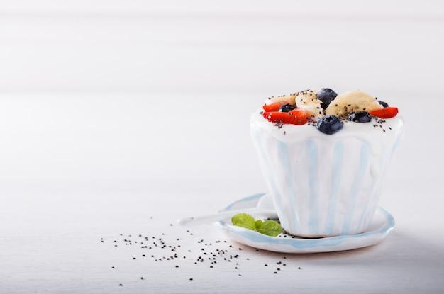Jogurt, domowej roboty w ceramicznej misce z jagodami