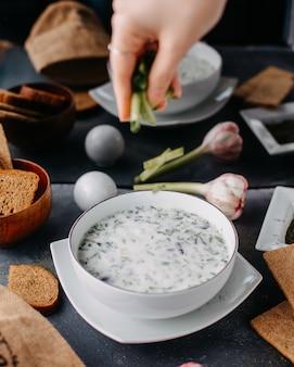 Jogurt dovga z zielenią wewnątrz okrągłego białego talerza wraz z jajkami chleba na szarym stole