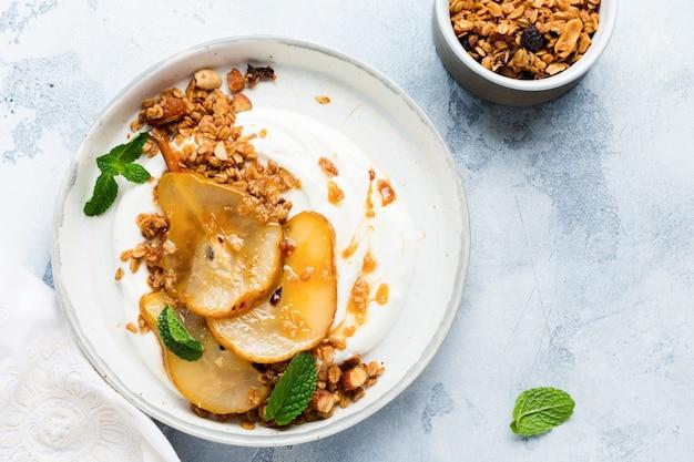Jogurt grecki z karmelizowaną gruszką, muesli, orzechami i stopionym cukrem na szarym talerzu ceramicznym