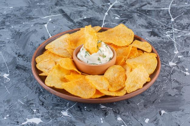 Jogurt i chrupiące chipsy ziemniaczane w talerzu, na marmurowej powierzchni