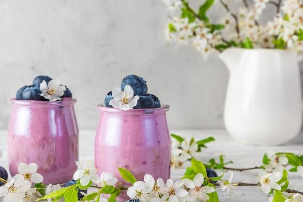 Jogurt jagodowy w szklankach ze świeżymi jagodami i wiśniowymi kwiatami wiśni w wazonie