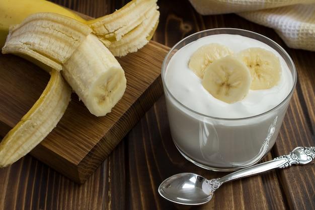 Jogurt mleczny z bananem na drewnianym stole