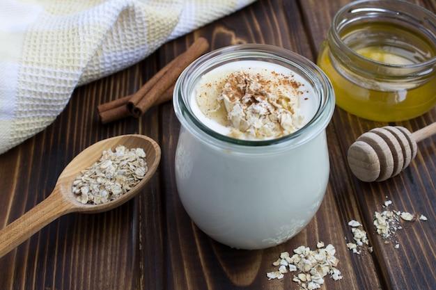 Jogurt mleczny z bananem, płatkami owsianymi i cynamonem na podłoże drewniane
