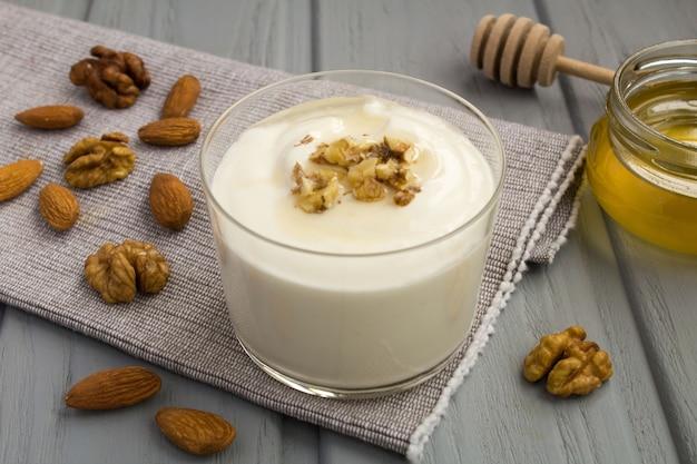 Jogurt mleczny z miodem i orzechami na szarej serwetce