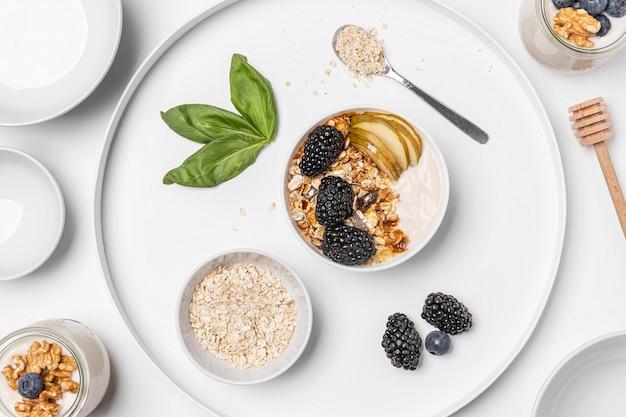 Jogurt na płasko z owsem, owocami i miodem na talerzu
