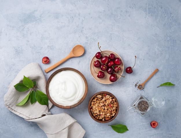 Jogurt naturalny z granolą i wiśnią na jasnym stole