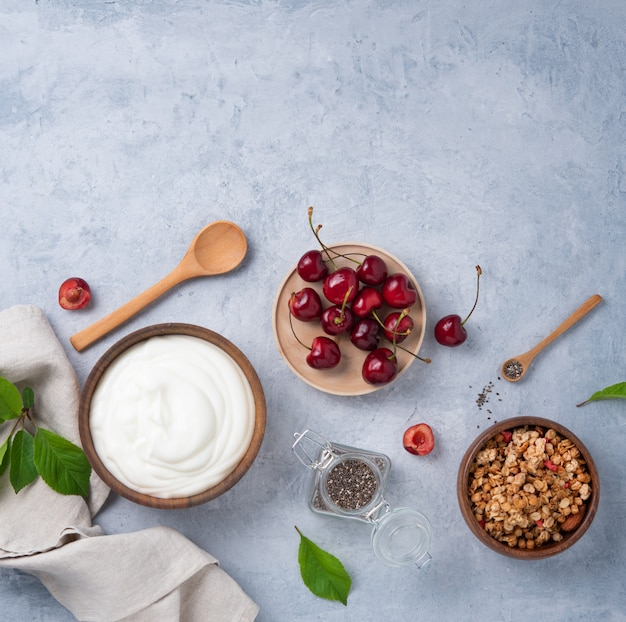 Jogurt naturalny z granolą i wiśnią na jasnym tle
