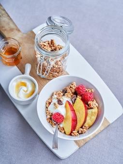 Jogurt naturalny z malinami i nektarynkami, miodem i musli na kuchennym stole. zostań w domu, zdrowe śniadanie. selektywna ostrość, miejsce na kopię. widok z góry.