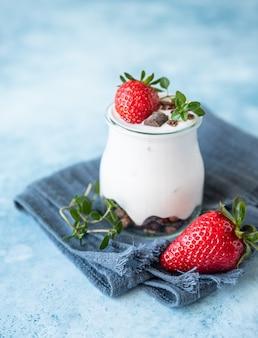 Jogurt naturalny z muesli i truskawkami na śniadanie lub przekąskę koncepcja zdrowego odżywiania