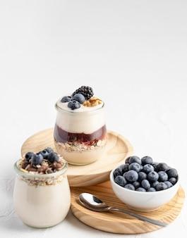 Jogurt o wysokim kącie wymieszać z owocami, dżemem i owsem