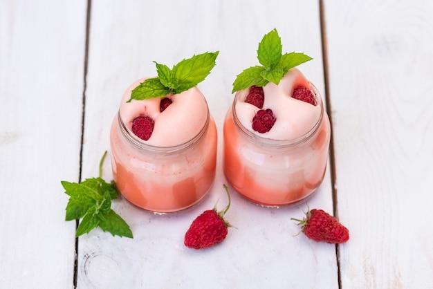 Jogurt owocowy na śniadanie. z naturalnymi plastrami malin, jagód i jeżyn