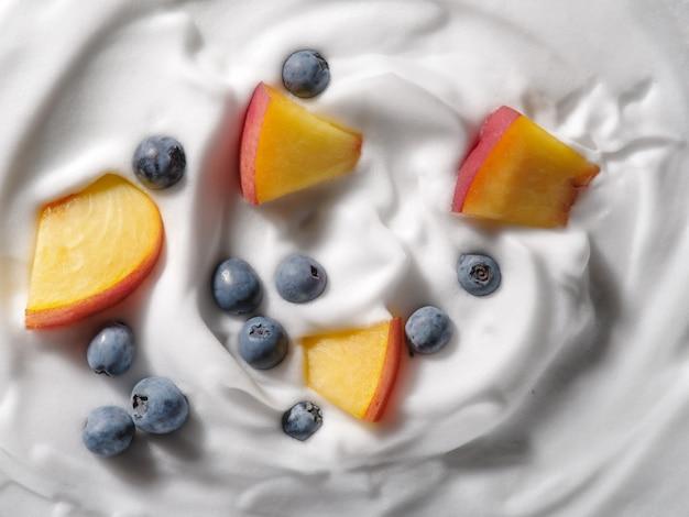 Jogurt z brzoskwinią i jagodami, tło. płaski świeckich, widok z góry. koncepcja projektu opakowania.