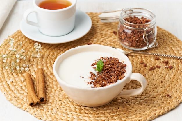 Jogurt z czekoladową granolą w filiżance, śniadanie z herbatą na beżu