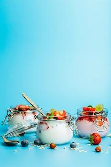 Jogurt z granola świeżymi jagodami i orzechami w słoiku na niebieskim tle zdrowe śniadanie i mleko...