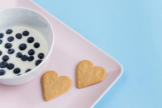 Jogurt z jagodami i ciasteczkami w kształcie serca na różowej tacy.