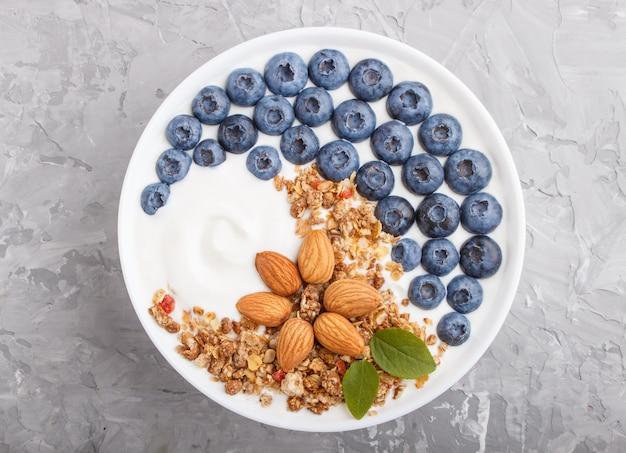 Jogurt z jagodami, muesli i migdałami w białej płytce na szarej betonowej powierzchni. widok z góry.
