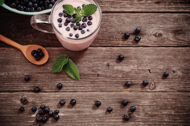 Jogurt z jagodami na starym drewnianym stole