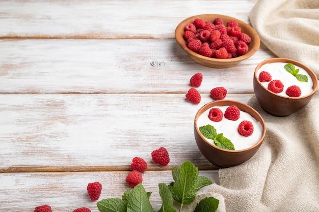 Jogurt z maliną w glinianych kubkach na białej drewnianej powierzchni i lnianej tkaniny