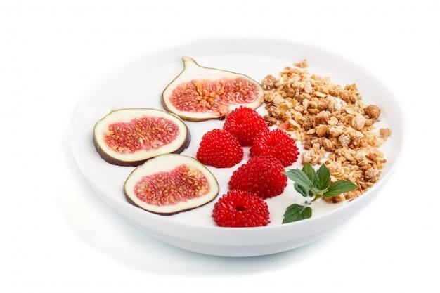 Jogurt z malinami, muesli i figami w bielu talerzu odizolowywającym na białym tle. widok z boku.