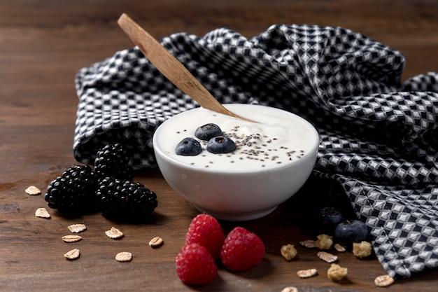 Jogurt z muesli i miską owoców