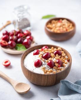 Jogurt z naturalnego fermentacji z granolą i wiśnią w drewnianej misce