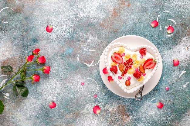 Jogurt z płatkami kukurydzianymi i jagodami w misce w kształcie serca.