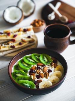Jogurt z różnymi owocami na drewnianym stole. pożywienie przydatne, dietetyczne, ekologiczne.