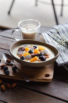 Jogurt z wiśniami, jagodami, ananasami, pitami, orzechami i mlekiem migdałowym na brązowym stole.