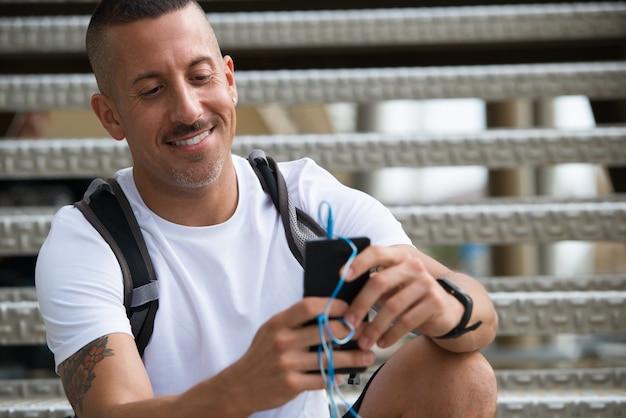 Jolly przystojny sportowiec czyta sms na urządzeniu