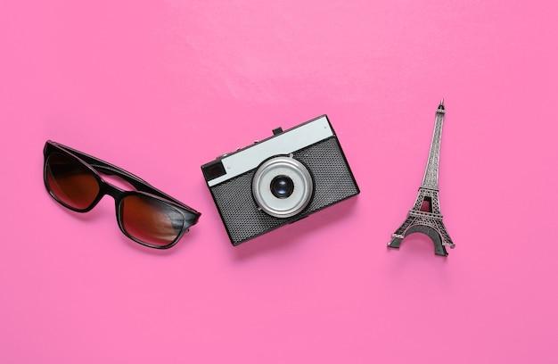 Jorney do paryża. okulary przeciwsłoneczne, aparat retro, figurka wieży eiffla na różowo