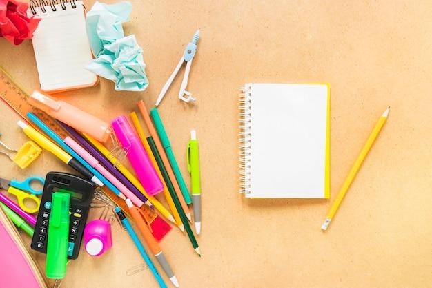 Jotter z ołówkiem i narzędziami do pisania ułożonymi w losowy sposób