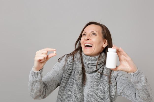 Jouful młoda kobieta w szarym swetrze, szalik patrząc w górę, trzymając tabletki leków, tabletki aspiryny w butelce na białym tle na szarym tle. zdrowy styl życia chory chory choroba leczenie koncepcja zimnej pory roku.