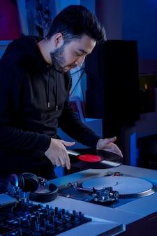 Joven dj colocando un disco de vinilo en un tornamesa para mezclar musica en una tienda de discos