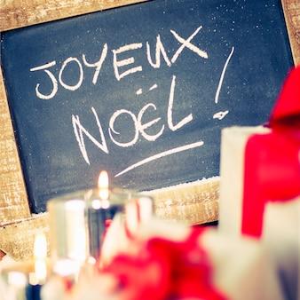 """""""joyeux noel"""" na tabliczce z prezentami i świecą."""
