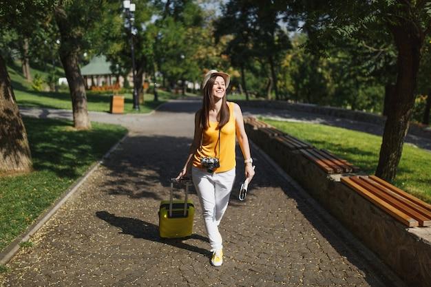 Joyful traveller turystyczna kobieta w żółtym letnim ubraniu i kapeluszu z walizką, mapa miasta spacerująca po mieście na świeżym powietrzu. dziewczyna wyjeżdża za granicę na weekendowy wypad. styl życia podróży turystycznej.
