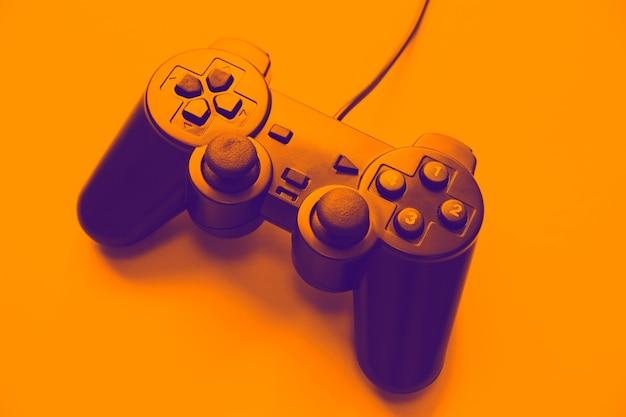 Joystick na pomarańczowym tle. gamepad do grania w gry komputerowe.