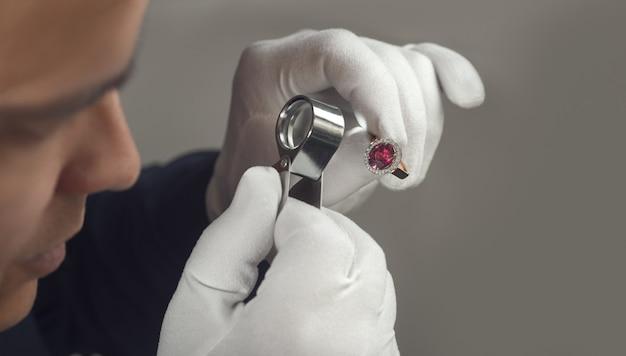 Jubiler przy pracy mężczyzna jubiler bada złoty rubin i diamentowy pierścionek jubiler mistrz złotnik bada...
