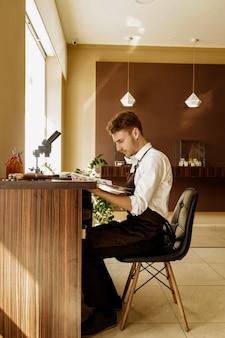 Jubiler rozważa katalog produktów siedzących w miejscu pracy