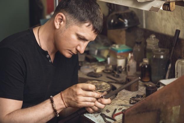 Jubiler sprawdza złoty pierścionek pod kątem wad w swoim warsztacie