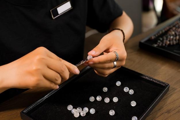 Jubiler wykonujący ręcznie robioną biżuterię z koralików kamiennych.