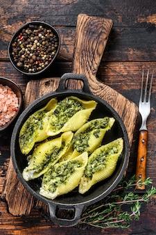 Jumbo muszle włoski makaron conchiglioni konkiloni faszerowane mięsem wołowym i szpinakiem. ciemne drewniane tło. widok z góry.